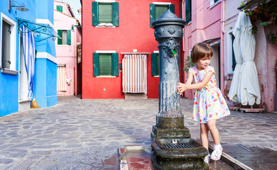 The girl washes hands in the fountain. The first acquaintance with  fountains of  island of Burano
