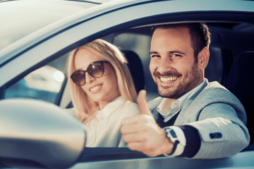 Young couple buying car at dealership center