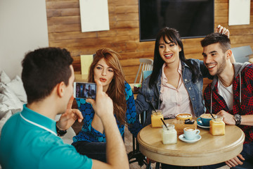 Young man photographing friends in a cafe with smartphone