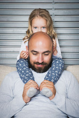 Happy family concept, father and daughter portrait, sitting on a couch having fun