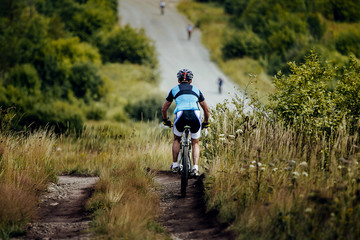 athlete cyclist mountainbiker descent from mountain on trail in grass