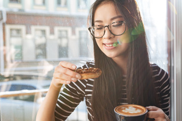 Young Asian woman eating cake on windowsill