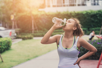 Beautiful Asian Sport Woman are Drinking Water After Running on Sunset Evening Summer Time