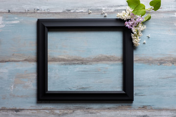 Picture frame with lilac flowers and copy space on blue wooden background