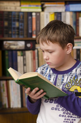 Child reading book at home. Boy in library