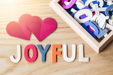 joyful wooden text alphabet on wooden table