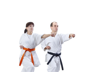 With black belt and orange belt the athletes are beating punch arm