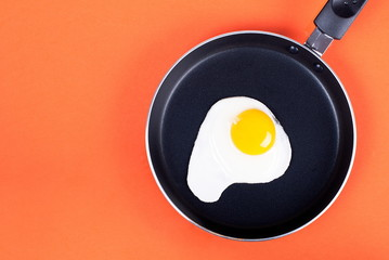 Aluminium Prints Egg fried eggs in a pan of one egg on an orange background