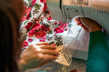 Making table decorations. A shot of woman sewing a natural linen tablecloth, towels and napkins with red rose print and a crochet white linen lace trim, using a sewing machine and needles
