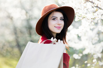 beautiful young woman with shopping bags standing in front of wonderful blooming trees background
