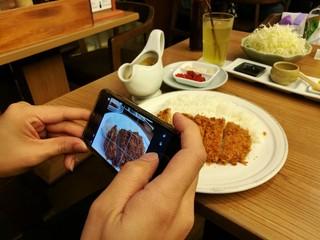 Takeing food photo before eating, Deep-fried pork slice in restaurant, Pork cutlet set, Japanese pork Tonkatsu, focus-on-foreground with blur background