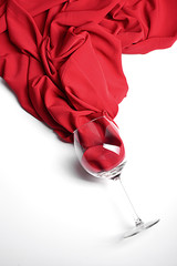 Overturned glass of wine on a white background with flowing red fabric