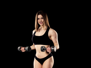 Young girl doing biceps exercise in the gym.
