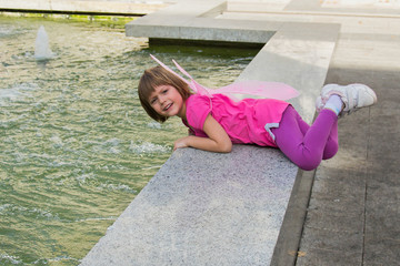 Little girl with butterfly wings having fun in a fountain