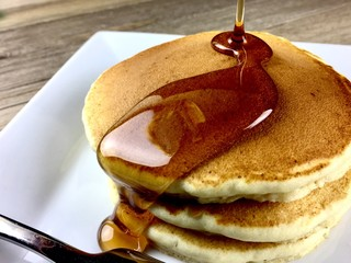 Stack of pancakes with maple syrup on a white plate