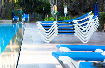Blue deck chairs arranged around the pool before or after the end of holiday