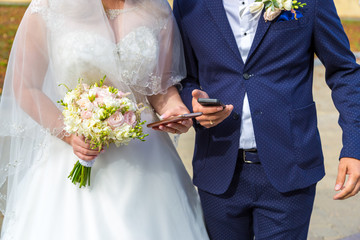 the bride and groom with mobile in hand. Modern wedding with gadgets