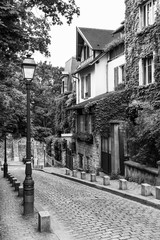 Charming old street of Montmartre hill in black and white. Paris, France