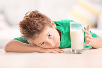 Cute kid with glass of milk sitting at a table