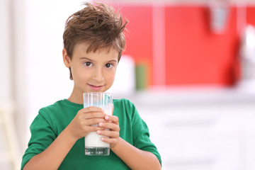 Little kid with glass of milk at kitchen