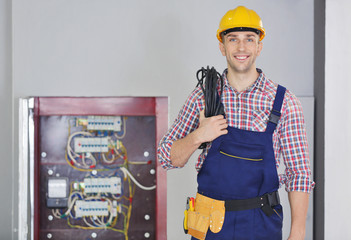 Young electrician with tools standing near open distribution board