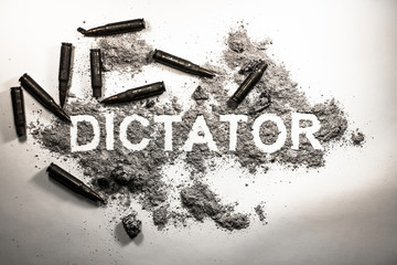 Dictator word written in  ash, dirt, dust with bullets around as dictatorship, power, war, revolution, tyranny, bad government or political system concept lent background