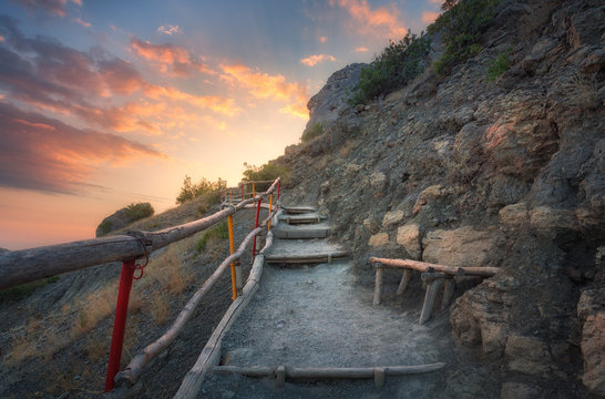 Stone stairs with wooden railing in the mountains at sunset. Landscape with mountain path and rocks against colorful blue sky with clouds. Trail leading to the mountain peak. Adventure and travel
