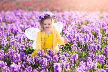 Wall Mural - Little girl in fairy costume playing in flower field