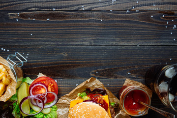 Fototapeta Fresh delicious burgers with french fries, sauce and drink on the wooden table top view, with copy space obraz