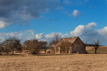 Old abandoned barn in the Czech countryside. Spring weather in the fields. Agricultural farm.