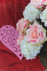 pink heart and white and pink cloth roses with a red background
