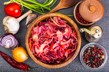 Salad of cabbage, carrots, beets and butter in a wooden bowl, re