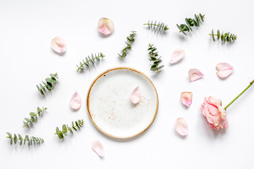 rose petals and eucalyptus on white table top view mock up