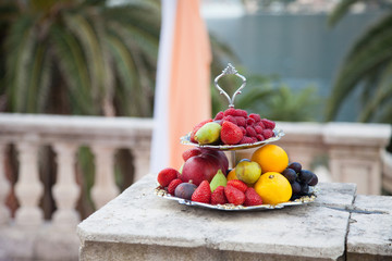 Wedding ceremony and dish with fresh fruits and berries near palm, sea, yacht, mountains.