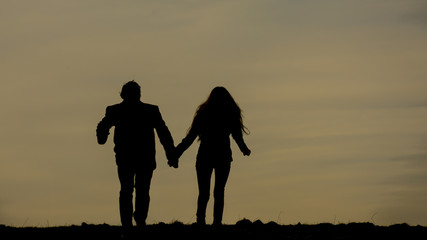 Silhouette of two people during sundown on the horizont.  Two running young peoples in love. Sport activity.