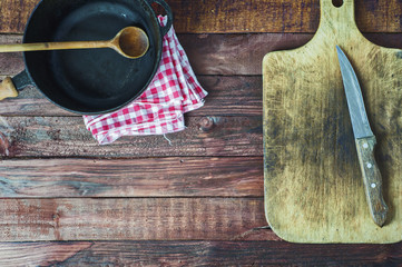 black cast iron pan and cutting board on brown wooden surface