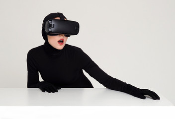 Young girl in black skin-tight suit, hood and gloves with VR headset.