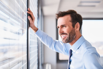 Happy businessman in office looking out the window