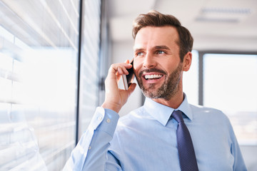 Businessman talking on the phone in office looking out the window