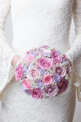 Pink and lilac wedding bouquet of roses, statice and gypsophila
