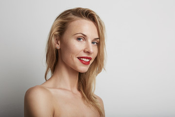 Portrait of beautiful young woman with blonde hair wearing red lipstick.