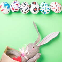 Easter bunny in a paper bag. Green background. Easter ideas. Easter eggs. Space for text.