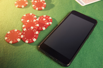 Smartphone on green gambling cloth next to poker chips