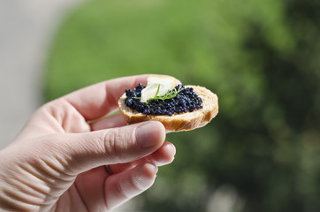 Woman hand with small piece of food