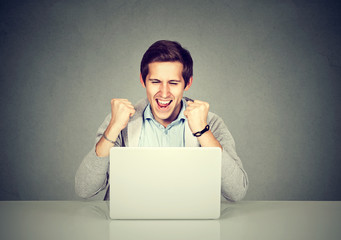 Man celebrating success in front of a laptop
