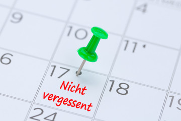 Nicht vergessent written on a calendar with a green push pin to remind you and important appointment.