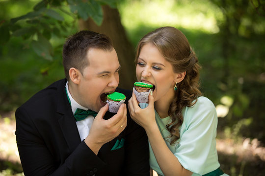 Man and woman eating green cupcakes in park. Crazy couple. Green wedding or saint patrick day