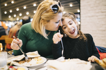 Mother And Daughter Eating In Restaurant