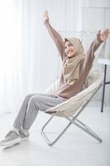 excited young woman with hijab raise her arm up while sitting on a couch