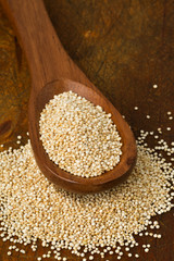 Raw, whole, unprocessed quinoa seed in wooden spoon on wood board
